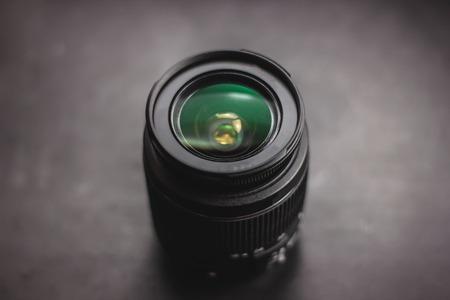 Closeup of camera lens over black background glass