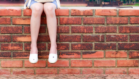 Young woman sitting on brick wall Foto de archivo