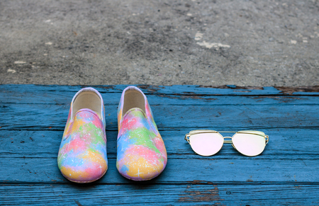 Pair of female summer shoes and sunglasses on blue wooden board