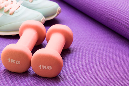 sport, healthy lifestyle and objects concept - close up yoga mat, sport shoes and dumbbells on purple background. Concept healthy lifestyle, sport and diet. Sport equipment. Copy space. Stock Photo