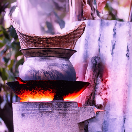 Antique steam cooking sticky rice in the countryside of Thailand.Sticky rice had steam in basket bamboo and old black pot on charcoal stove. Vintage tone.