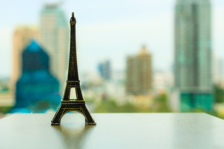 Model of the Eiffel Tower on a table behind cityscape scene in the office. Destination of tourists. Intent to go once.