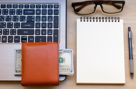 workspace with wallet, banknotes, laptop, eyeglass, notebook and pen on wooden table.