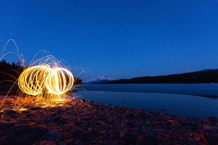 steel wool: Burning steel wool near a lake at night under the stars