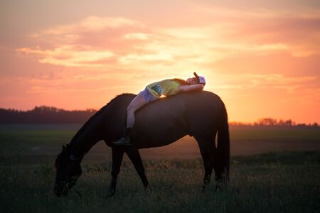 Girl lying on her horse without a sadle relaxing while it eats grass Reklamní fotografie