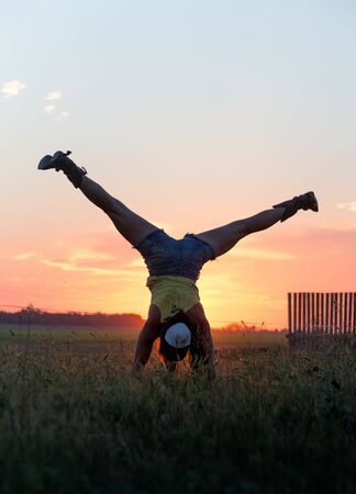splits: Girl doing handstand and splits in a field at sunset