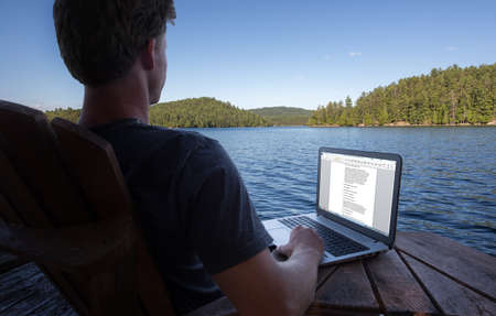 writing western: Young caucasian man working on laptop while on vacation to the lake Stock Photo