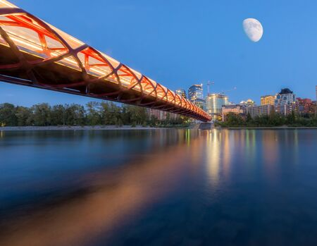 blue hour: Bridge over water in front of buildings with moon blue hour