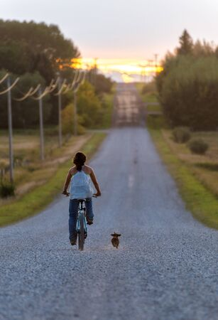Farm girl bikes down dirt road with dog at sunset Stock Photo