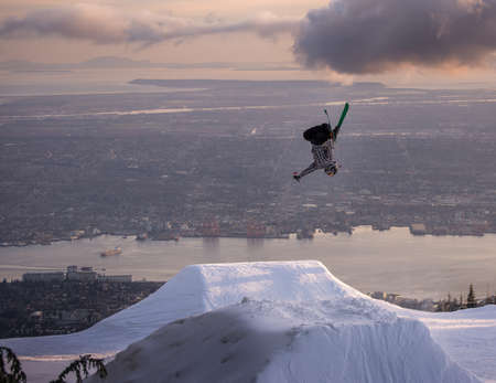 BACKFLIP: Freestyle skier performs backflip mute grab on jump over city