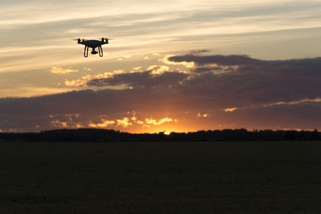 Drone silhouetted against orange sunset taking video