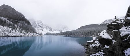 Panorama of Moraine lake after a fresh dusting of snow with man on rock