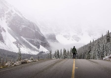 winter escape: Photographer walks down a road in the winter holding his camera Stock Photo