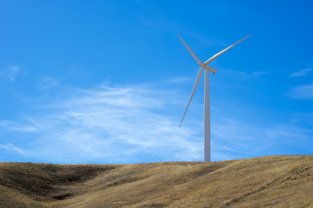 Single wind turbine on top of a hill with blue sky Stock Photo