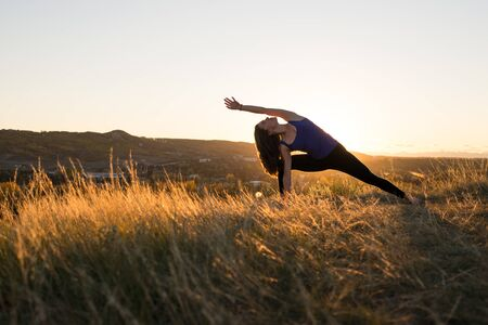 side angle pose: Woman doing yoga extended side angle pose during evening sunset