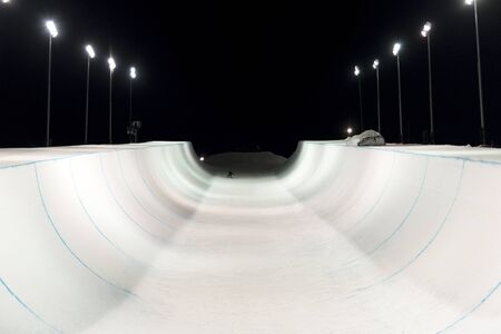 Snowboarder in a snow halfpipe night lit up by lights Stock Photo