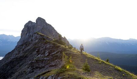 Male hiker walks along a ridge of mountain during sunrise