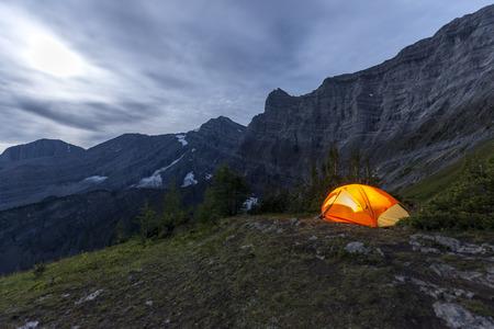 Illuminated tent camping on ridgeline of a mountain Stock Photo
