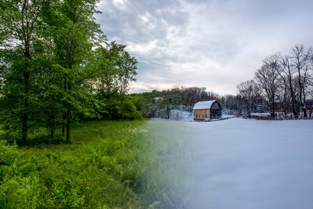 Transition photo from summer to winter of barn and trees in a field Stok Fotoğraf