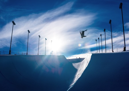 Skier doing an inverted trick in winter snow halfpipe 版權商用圖片