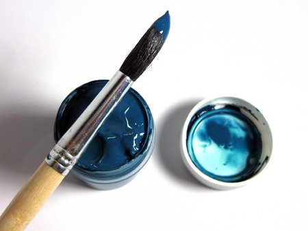 Paintbrush with blue paint, lying on bank with paint Stock Photo