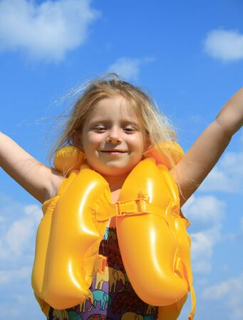 The happy girl in a life jacket
