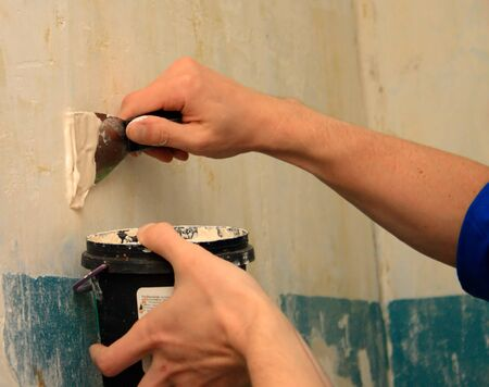 human arm(hand) repairs a wall (focus on right hand)