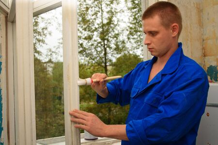 worker repairs(paint) a window in house Stock Photo