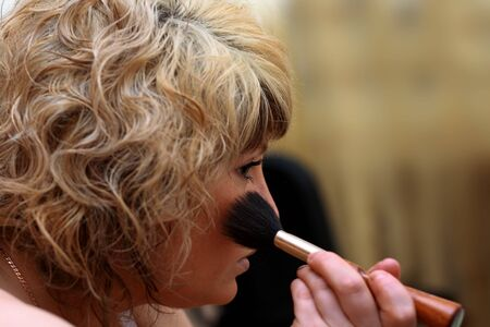 Young woman having powder applied