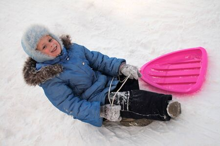 A little girl out playing in the snow. Sleigh riding