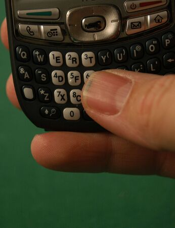 Thumb on the keypad of a smart phone