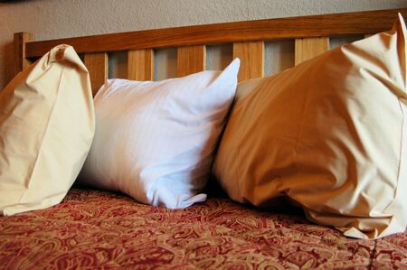 three pillows on a bed in a hotel room Imagens
