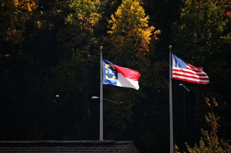 North Carolina and American flag blowing in the breeze