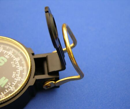 Closeup view of a compass on a blue background