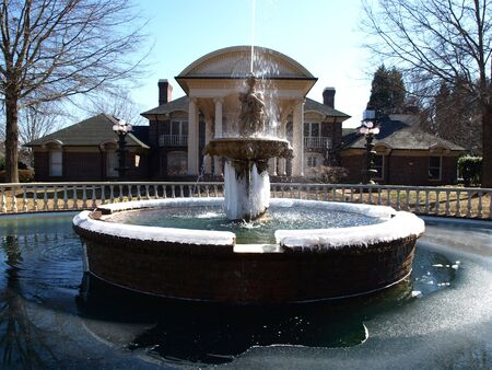 A cold frozen fountain and pond in front of a mansio