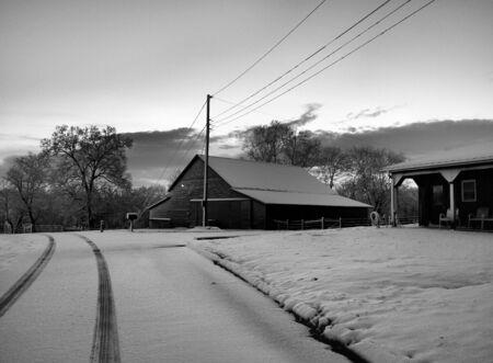 een boerderij in de winter in zwart-wit weergegeven