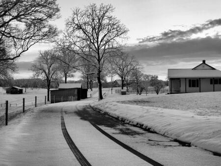 winter road: a farm in winter shown in black and white Stock Photo