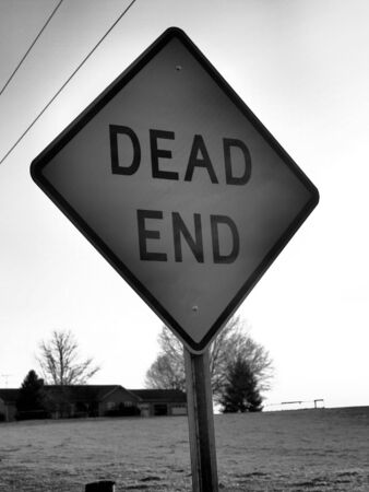winter road: Dead end sign in the winter shown in black and white