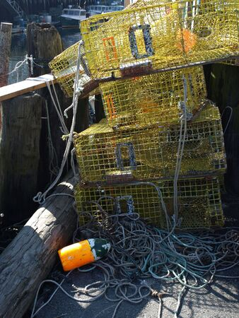 lobster boat: A working lobster boat along the dock in Portland, Maine during the summer with traps ready to load
