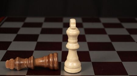 knocked over: Two kings on a chess board with one knocked over