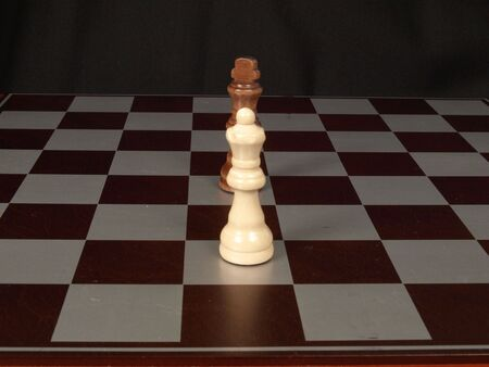 White king, black queen on a chess board