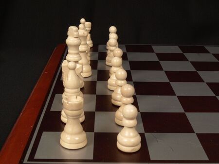 Row of white chess pieces ready to start the game