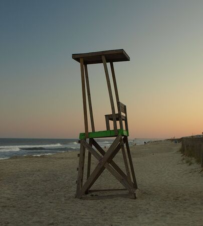 end of a long day: An empty lifegaurd chair at the end of a long summers day. Stock Photo