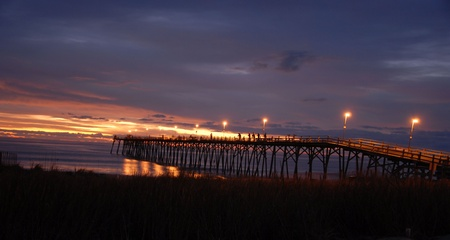 The sunrise over the pier at Kure Beach.  Stock Photo - 11265187