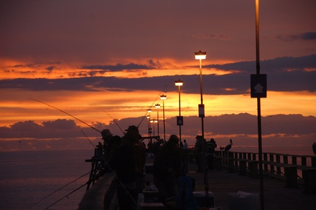 sportman: The sunrise over the pier at Kure Beach  with fisherman on the pier.
