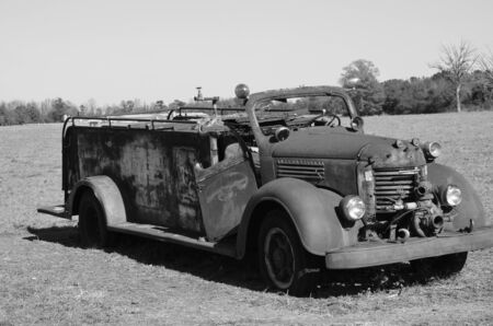 antique fire truck: Old rusted firetruck in the field shown in black and white.