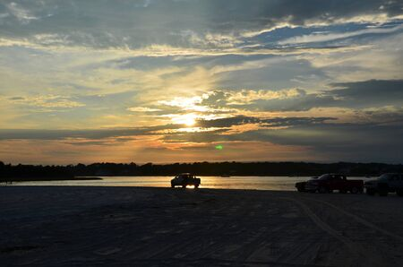 north   end: The north end of Carolina Beach at sunset, with a car parked near the water