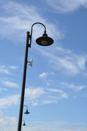 lighted: Street light with a curved lighted shown during the day.