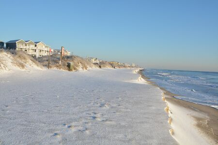 A rare snow and ice storm in Kure Beach North Carolina with snow on the beach.