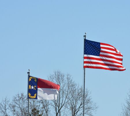 American and North Carolina flags flying in the breeze during the spring of the year.